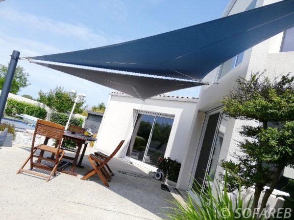 Vue du dessous de deux voiles dombrage bleues qui couvrent la terrasse de maison contemporaine