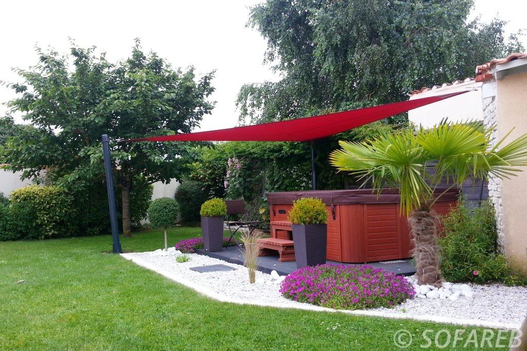 Voile dombrage triangulaire rouge installée dans un joli jardin et qui protège un jaccuzzi