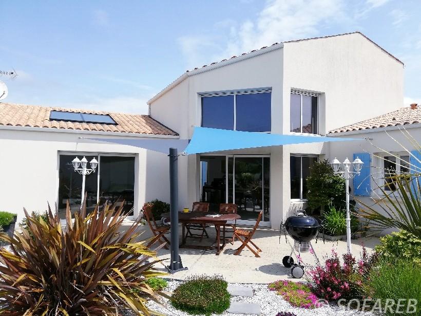 Voiles ombrage triangulaire Sofareb bleues claires et bleues foncées adossée à une maison contemporaine