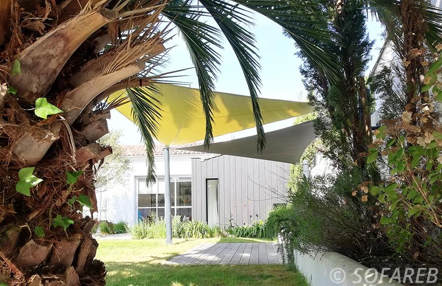 Voiles dombrage noire et verte au dessus de la terrasse en bois dune maison sur ile de ré