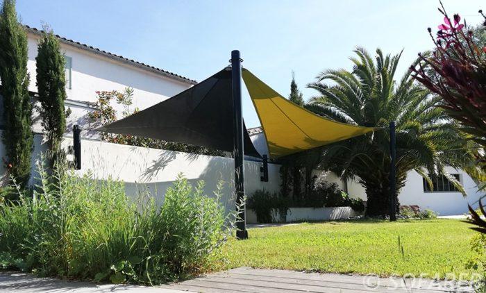 Grandes voiles dombrage triangulaires et étanches fabriquées sur-mesure par Sofareb en Vendée avec des tissus Serge Ferrari, et installées pour des clients à Rivedoux Plage