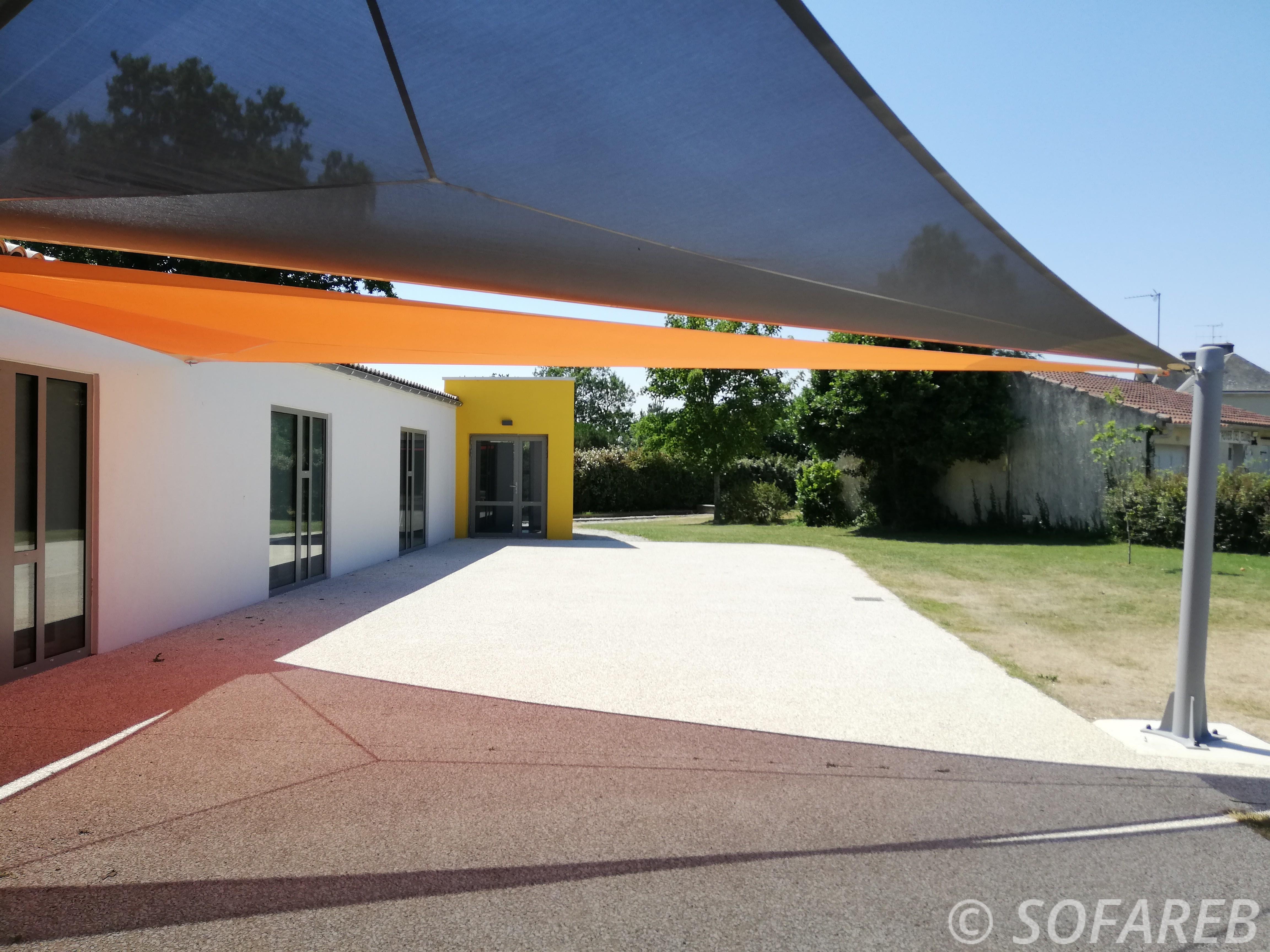 Deux voiles dombrage vue du dessous installées pour ombrager lespace extérieur de la Mairie de Thorigny en Vendée