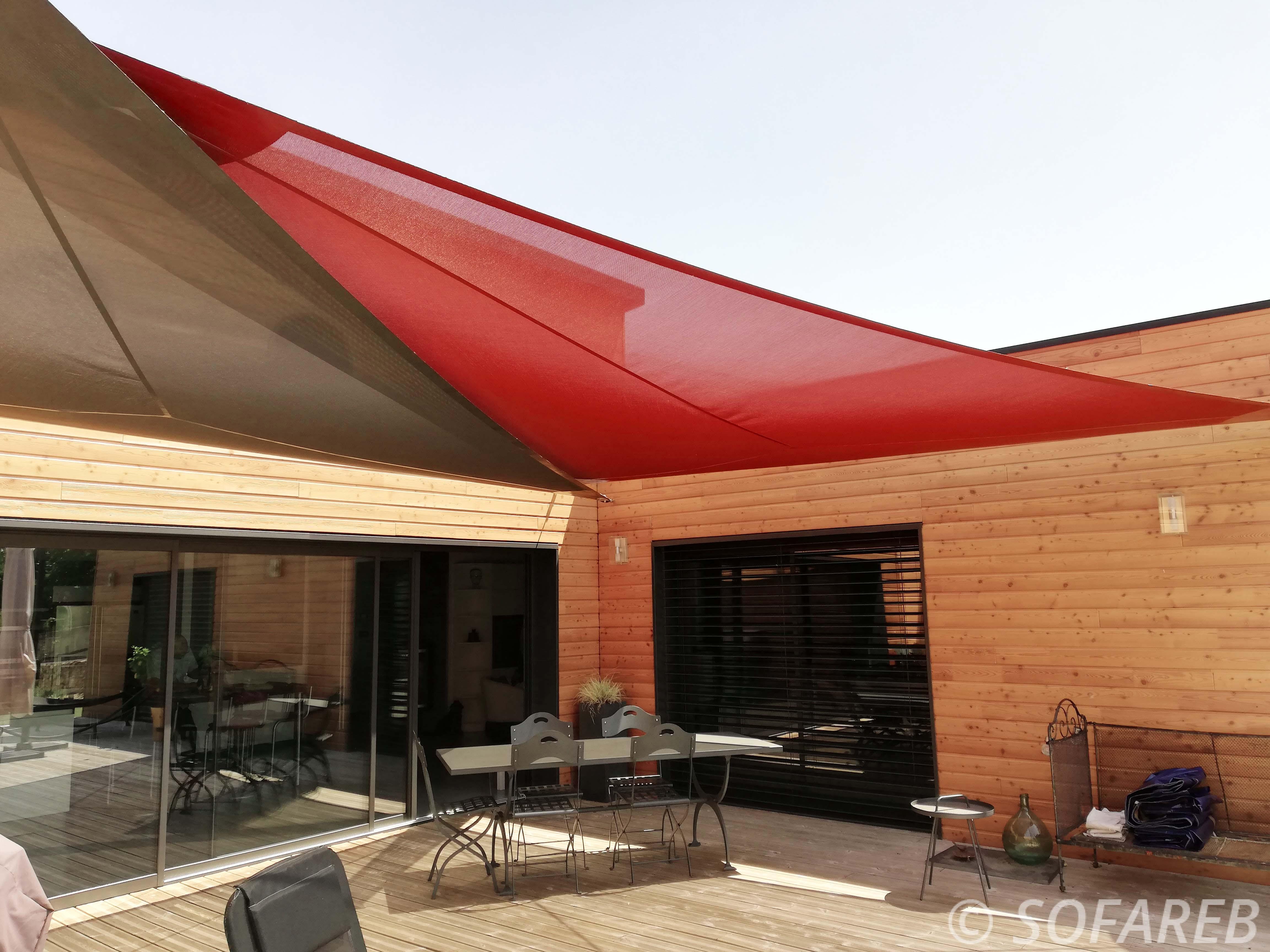 Deux grandes voiles dombrage triangulaires marron et rouge accrochées au dessus de la terrasse dune maison en bois et fabriquée par Sofareb avec des tissus Serge Ferrari