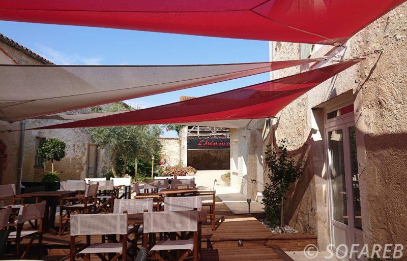 Vue du dessous de quatre grande voiles dombrage triangulaires occultantes installées au dessus de la terrasse dun restaurant en Vendée
