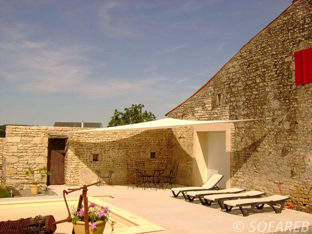 voile-d'ombrage-qualite-professionnelle-particulier-sur-mesure-mesures-vendée-qualité-france-française-Sofareb-local-expérience-particulier-professionnels-protection-solaire-terrasse-exterieur-design-moderne-jardin-ombre-ombrage-architecte-shadesail-blanche-maison-pierres