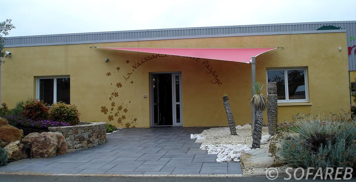 voile-dombrage-triangulaire-rouge-et-impermeable-installee-devant-l'-entree-d-un-magasin-en-vendée