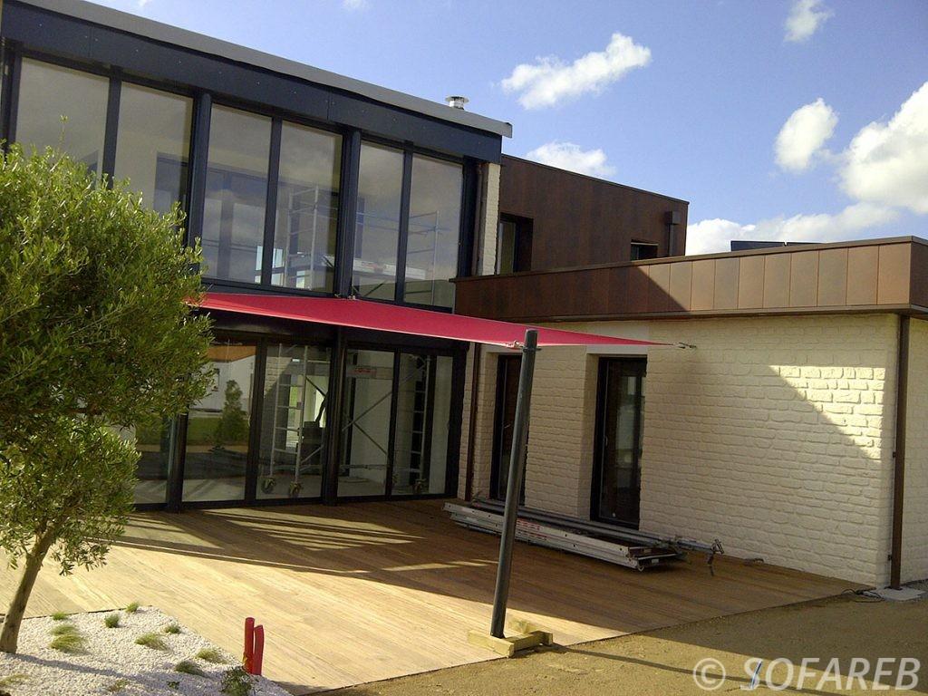 Voile d'ombrage rouge accrochées à la façade d'une maison en pierre contemporaine
