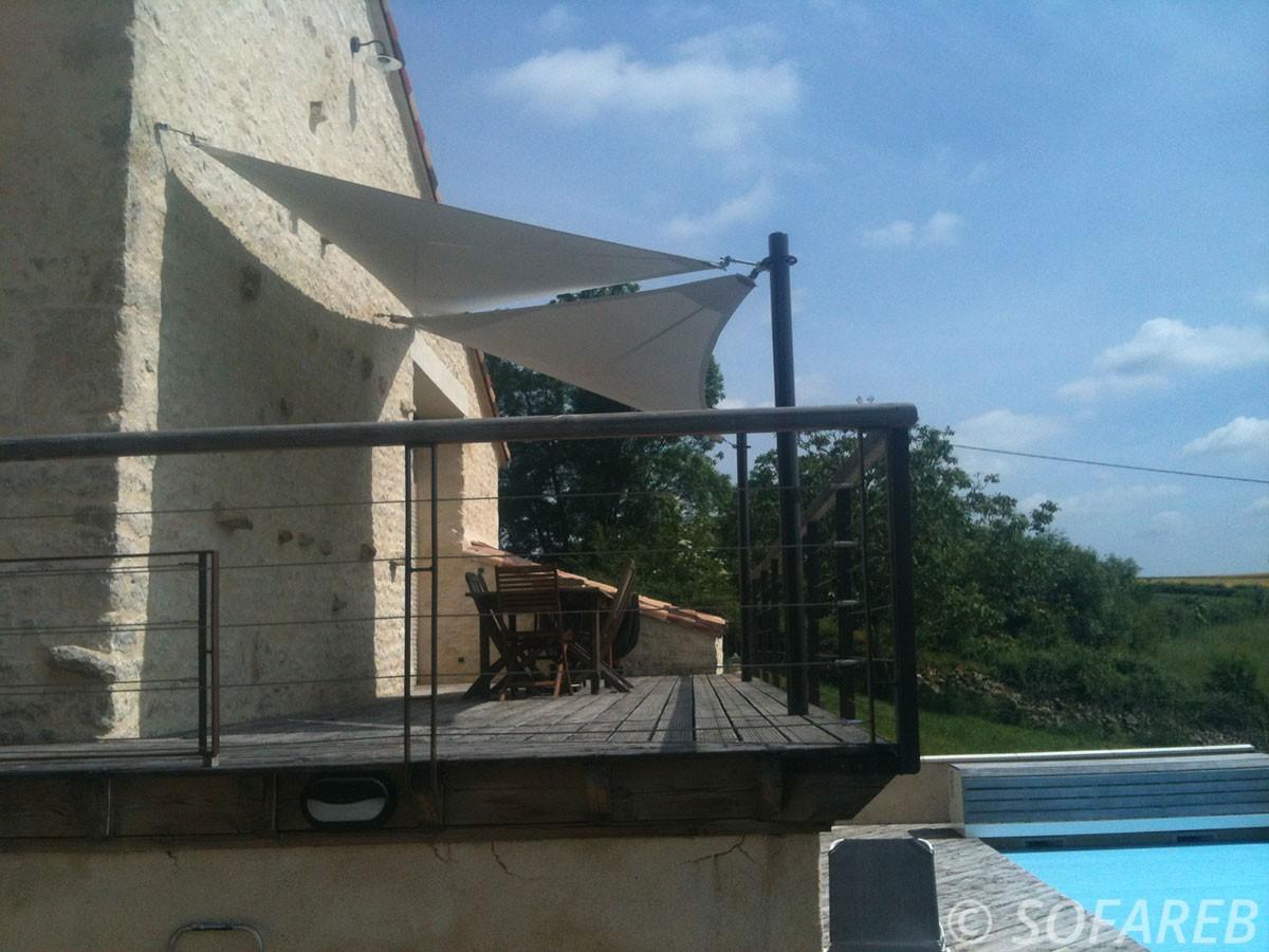 Voiles d'ombrage posées au dessus de la terrasse en bois surélevé d'une maison, avec une piscine en contrebas