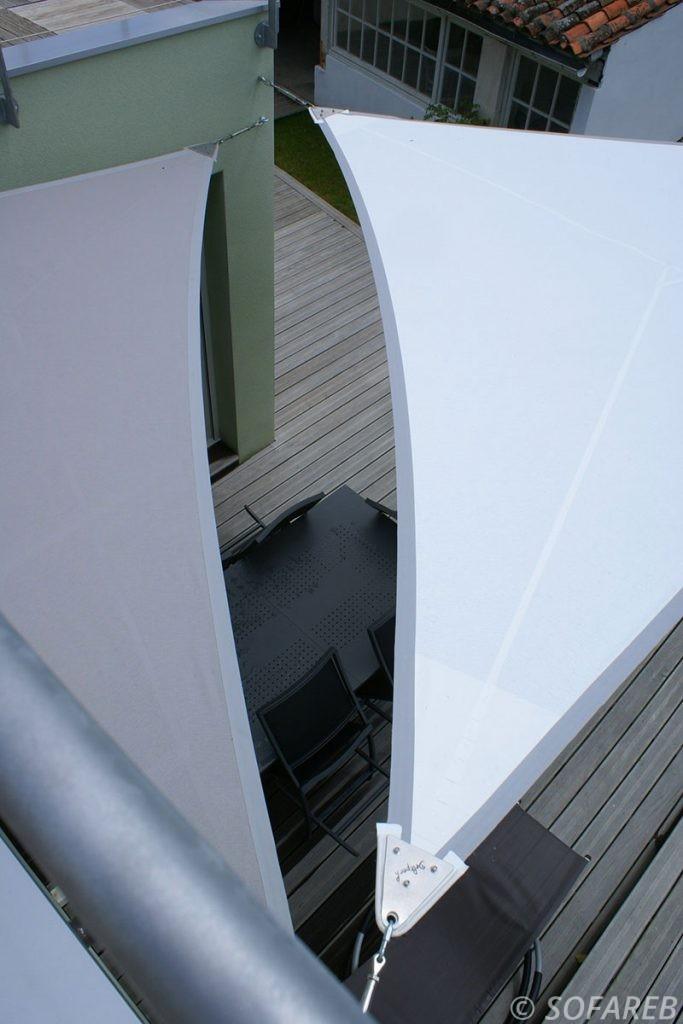Vue de pres du système d'accroche d'une voile d'ombrage triangulaire blanche