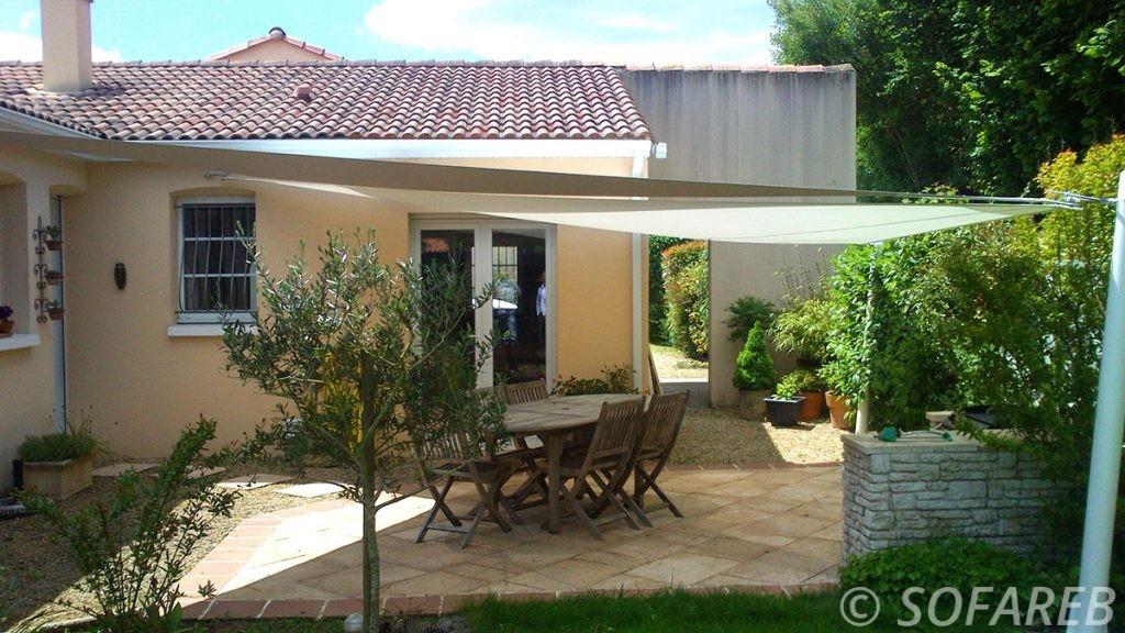 voiles d'ombrage imperméables blanche et marron au dessus d'une terrasse de maison plein pied