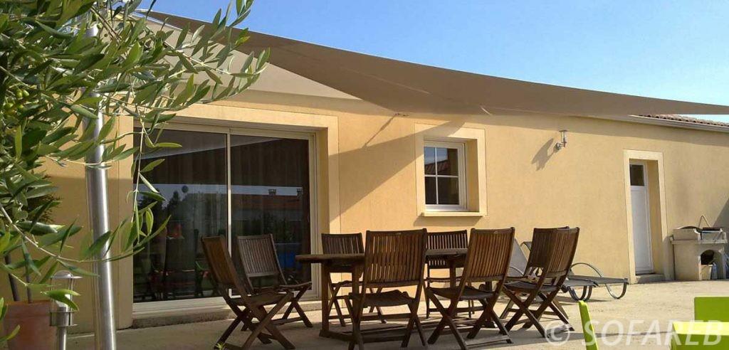 Façade d'une maison avec une voile d'ombrage triangulaire accrochée dessus