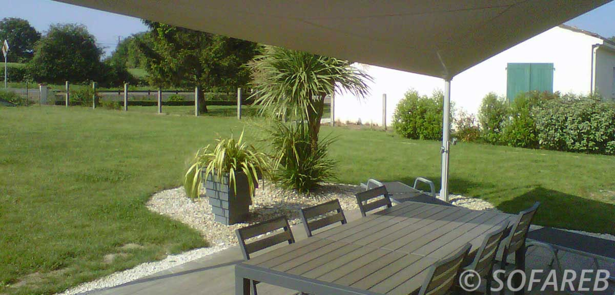 Grande voile d-ombrage qui abrite la terrasse et la table à manger d-une maison