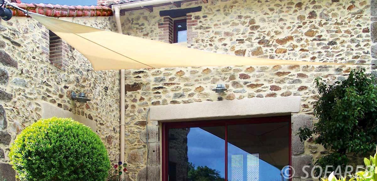 Voile ombrage sur-mesure beige adossée a la devanture d-une maison avec un revetement en pierre