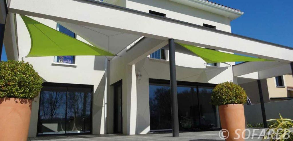 Vue en contre plongée de voiles dombrage triangulaires occultantes vertes et blanches placées par l-equipe sofareb au dessus de la terrasse d-une maison design