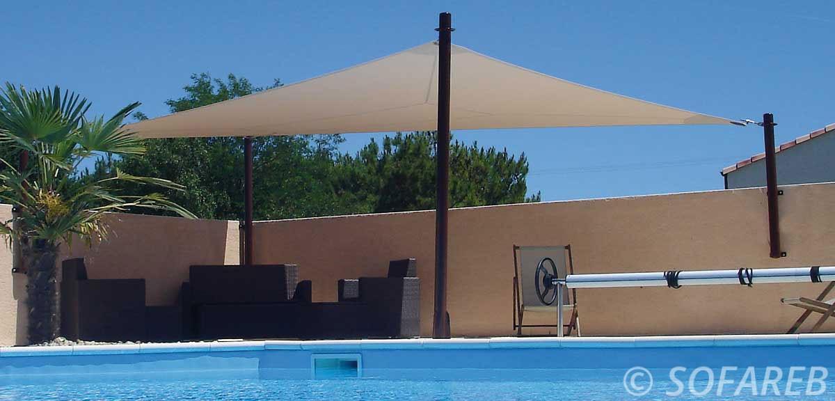 voile dombrage triangulaire de couleur beige avec des attaches sur-mesures posées devant une piscine par l-équipe sofareb