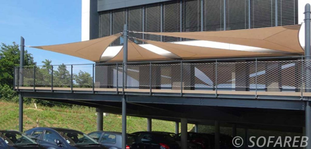 Voiles dombrage triangulaires grand format installée au dessus du balcon dun immeuble