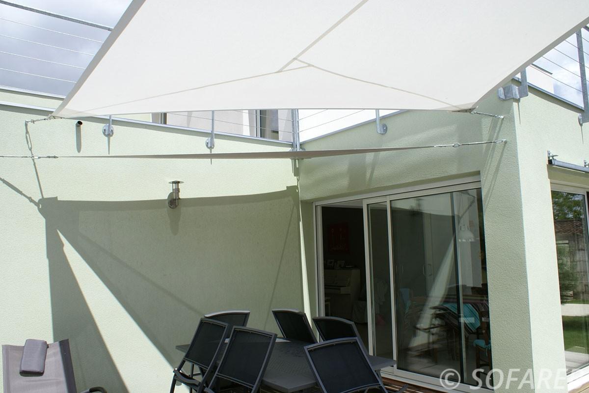 Dessous d'une voile dombrage rectangulaire concu sur-mesure par Sofareb et installée au dessus d'une terrasse avec des mobiliers de jardin