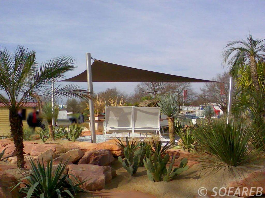 Voile d ombrage triangulaire sur-mesure et marron qui protege du soleil des transats dans un jardin