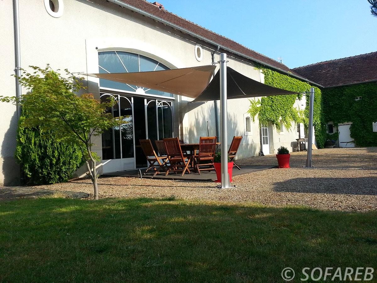 Voiles dombrage triangulaires beiges et marrons fabriquées en Vendée et posées dans le grand jardin dune ancienne ferme