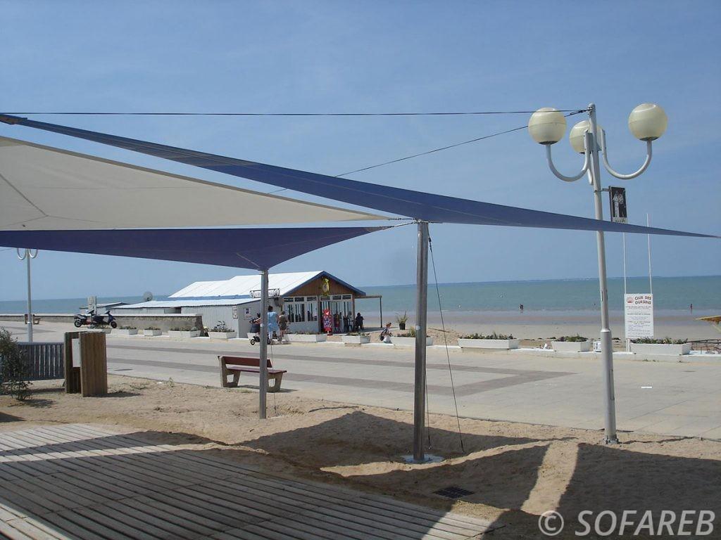 Voiles dombrage triangulaires grand format et de qualité installées au dessus de la terrasse d'un restaurant situé au bord de la mer