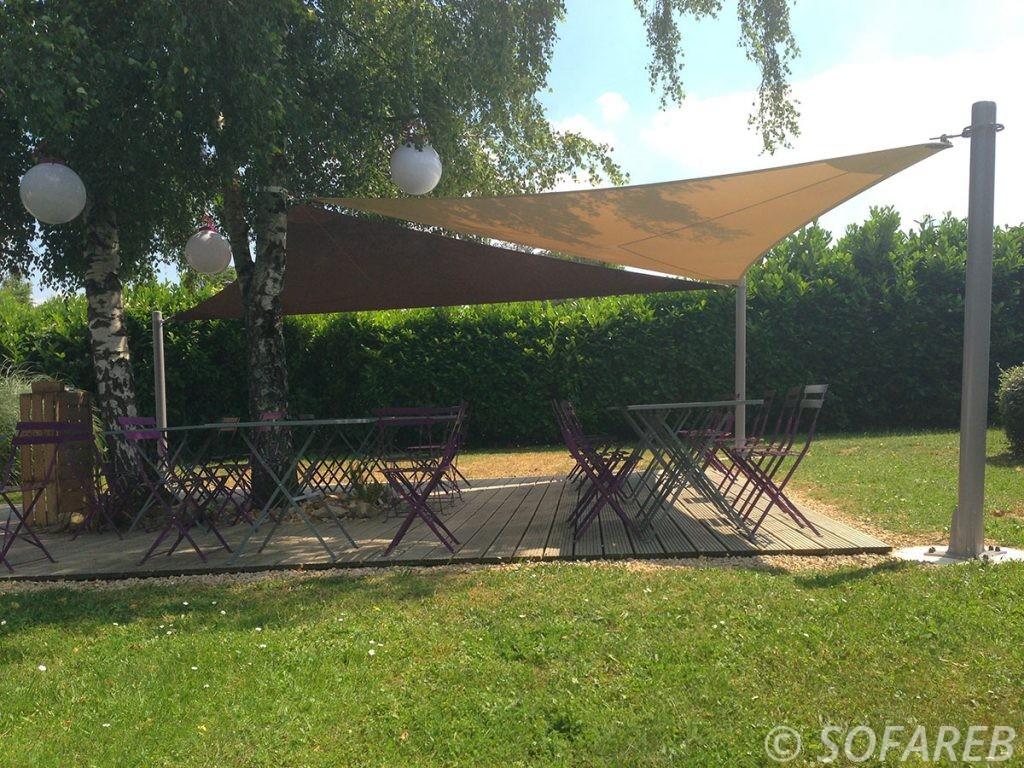 Voiles dombrage triangulaires beiges et marrons qui protege du soleil la terrasse dun restaurant en vendee