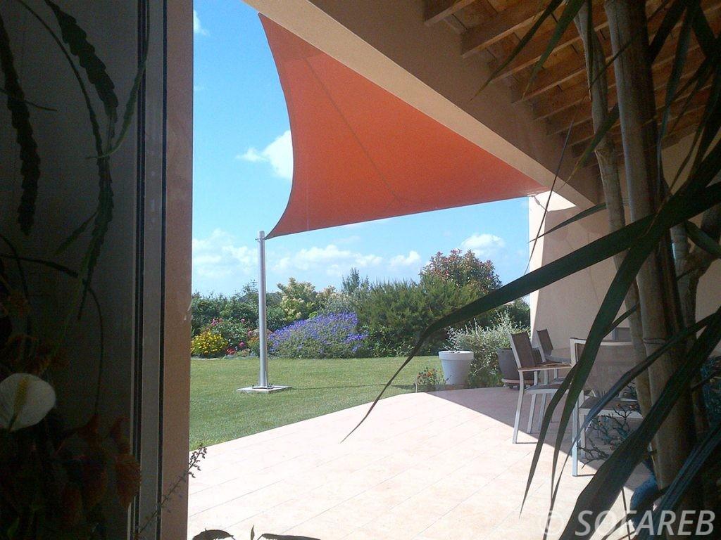 Vue du dessous d'une voile dombrage sur-mesure imperméable orange fabriquée par Sofareb en France et installée dans un jardin