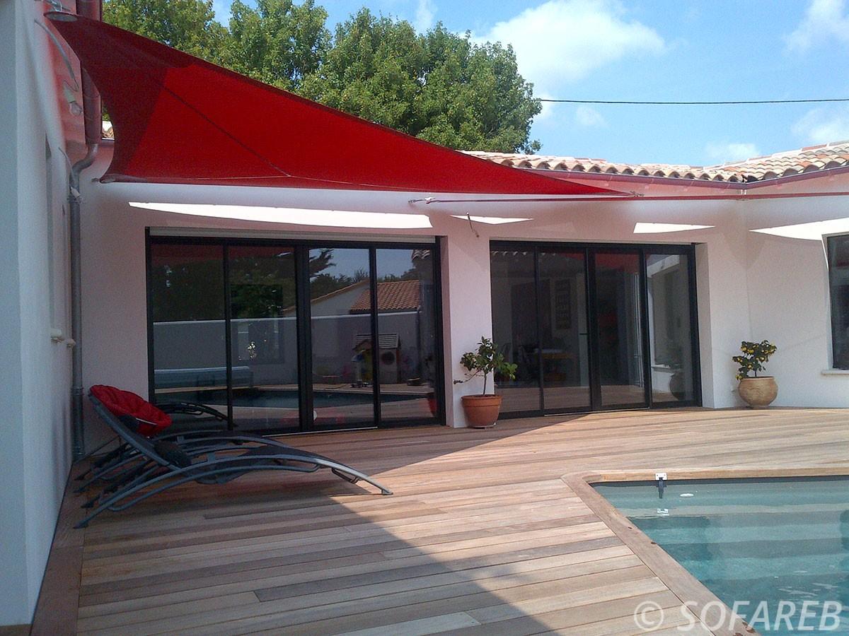 Voiles dombrage triangulaire rouge design fabriquée avec des tissus Serge Ferrari et accrochée au dessus de la terrasse en bois dune maison contemporaine