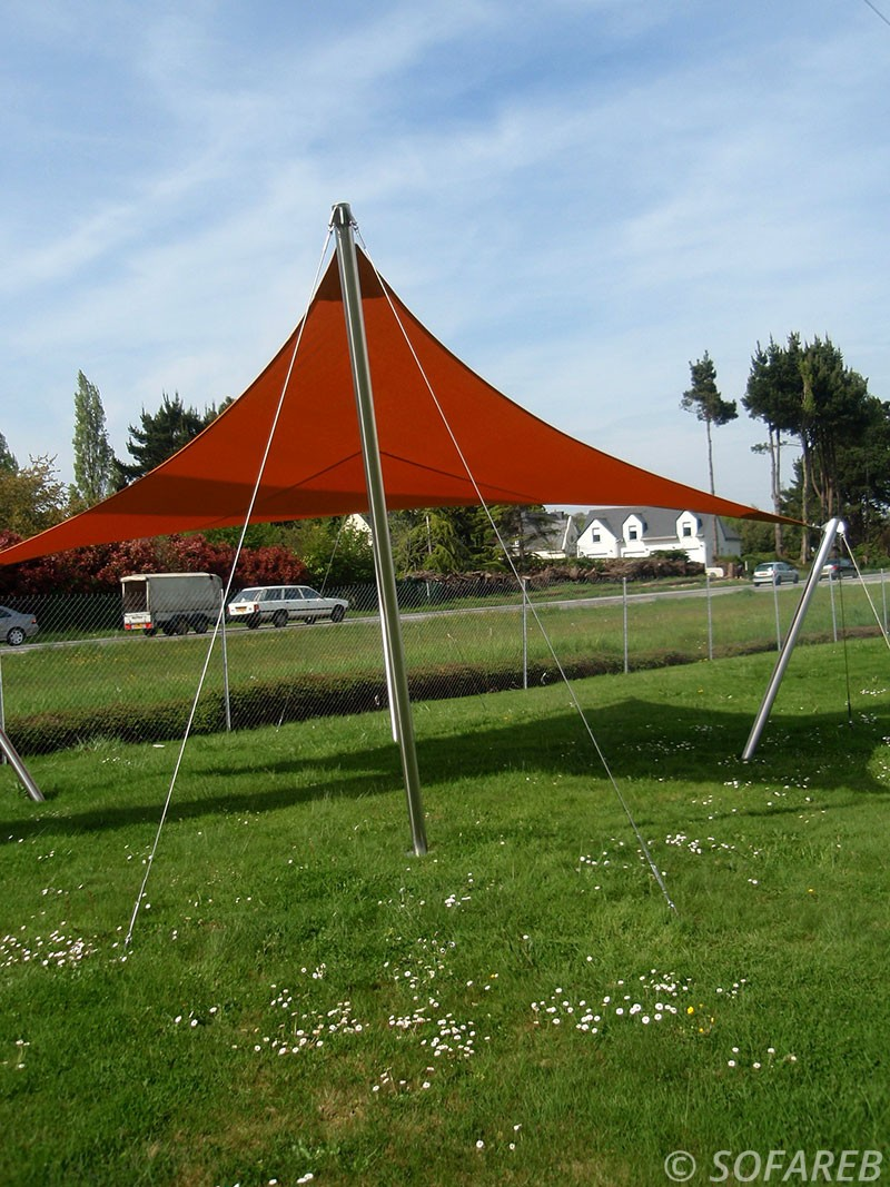 Voile dombrage imperméable sur-mesure en double courbure installée dans un jardin en Vendée