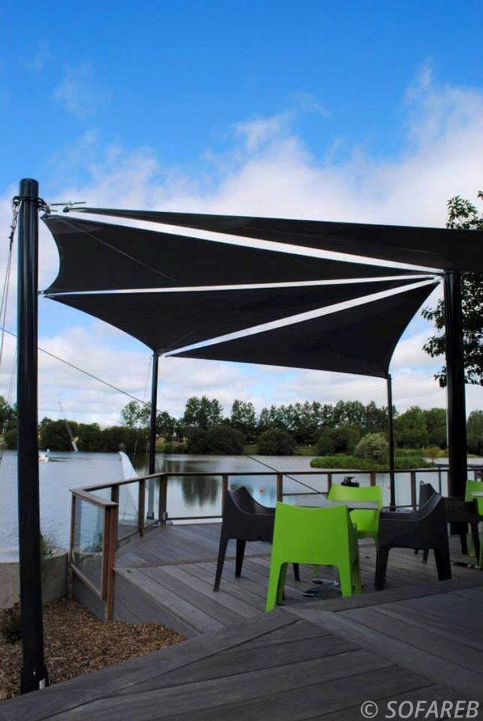 Voiles d'ombrage noires fabriquées par Sofareb pour la terrasse d'un restaurant près d'un lac en Vendée