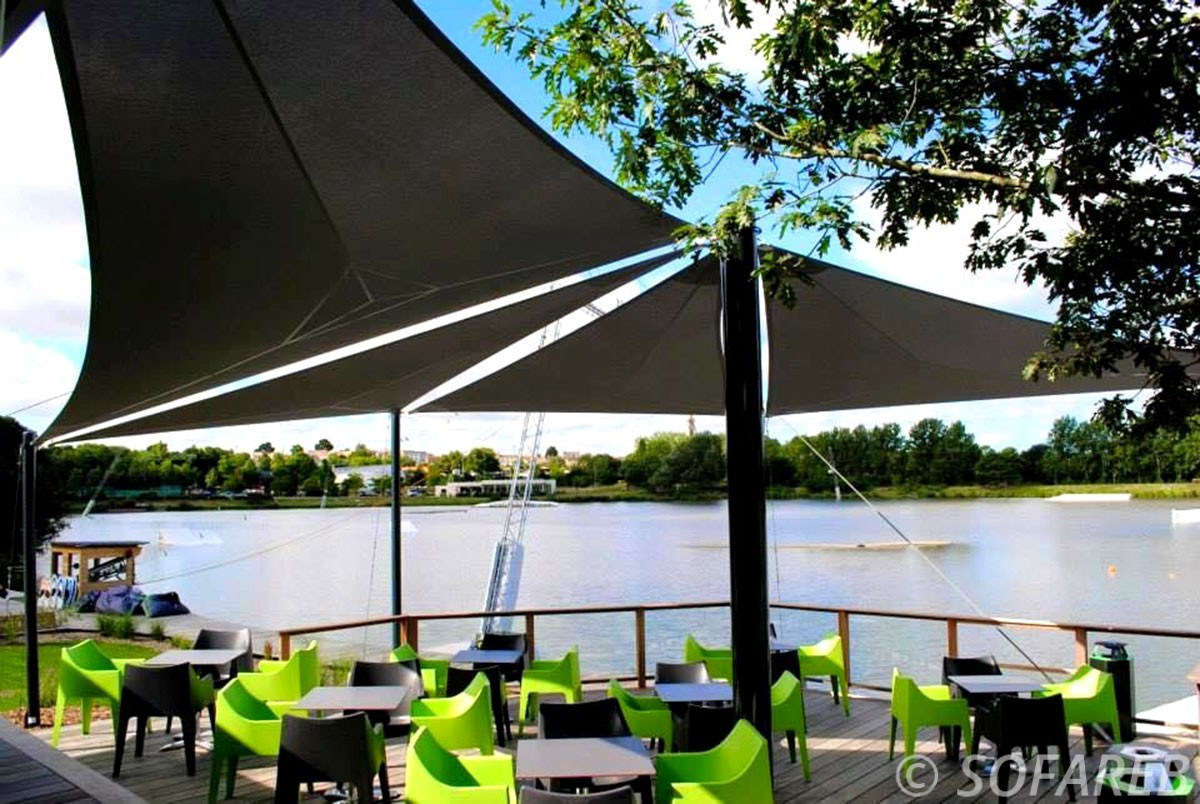 Trois grandes voiles d-ombrage noires anti-uv qui couvre la terrasse d-un restaurant pres d-un lac