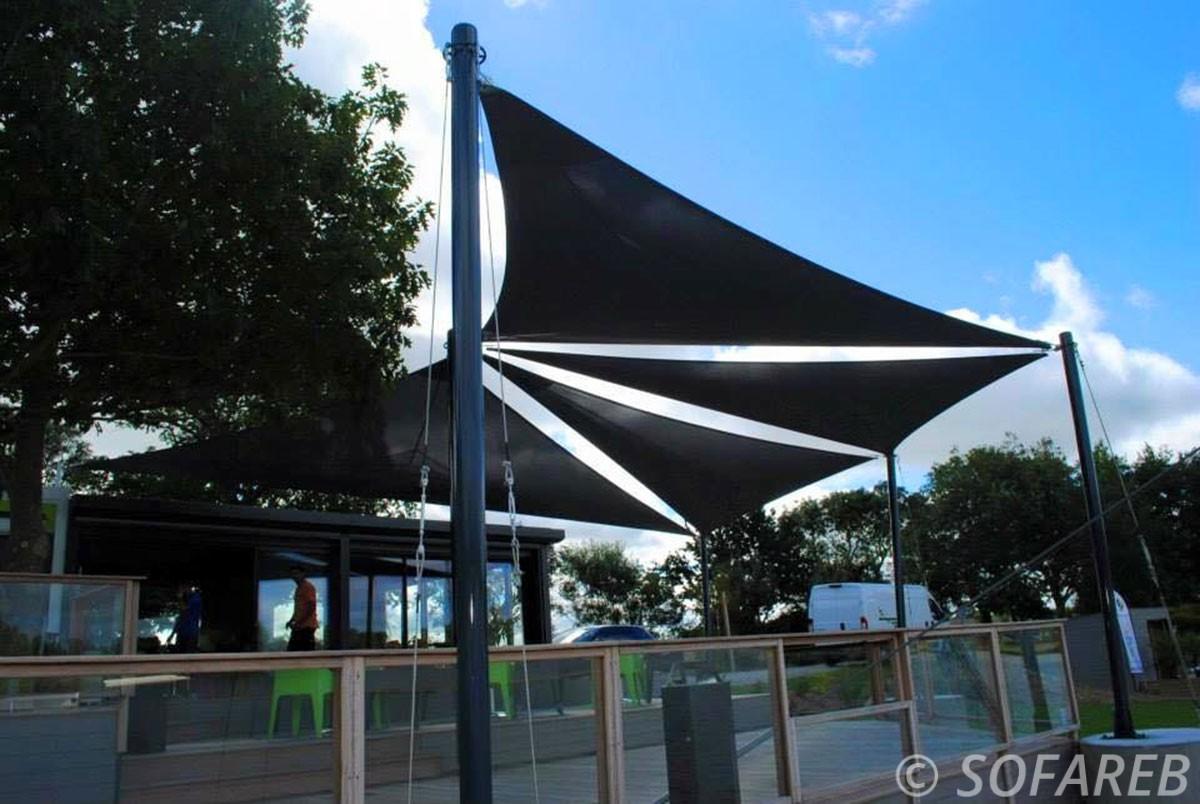 Vue en contre-plongé de 4 grandes voiles d'ombrage noires qui ombrage la terrasse d'un restaurant