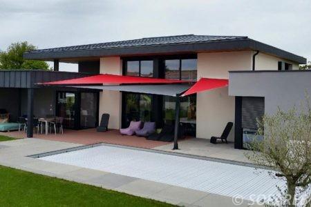 voile d-ombrage rouge et gris sur terrasse devant piscine