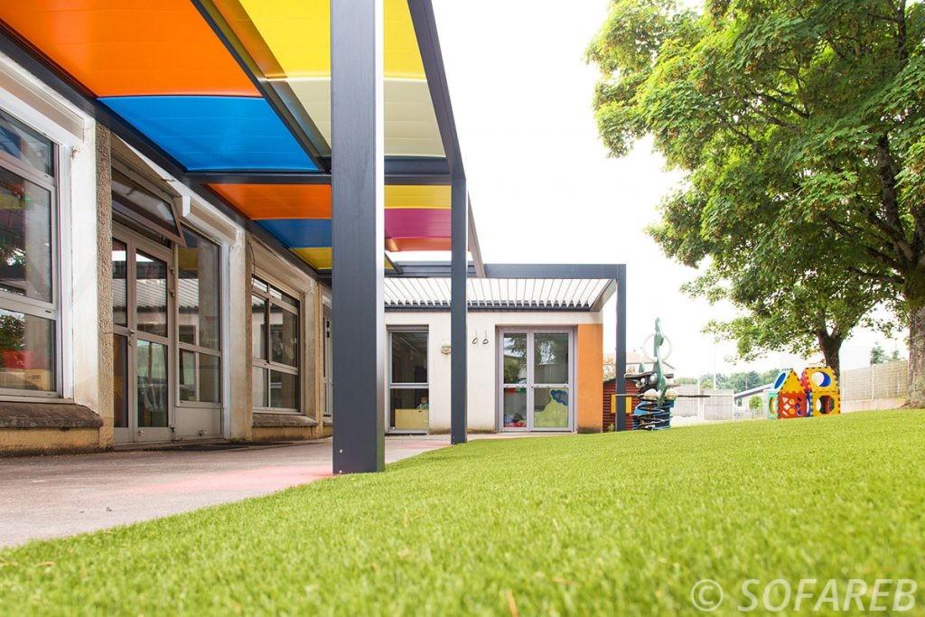 plan en contre-plongée pergola colorée adossée à une école primaire + pergola bioclimatique blanche à coté de jeux pour enfants et coures
