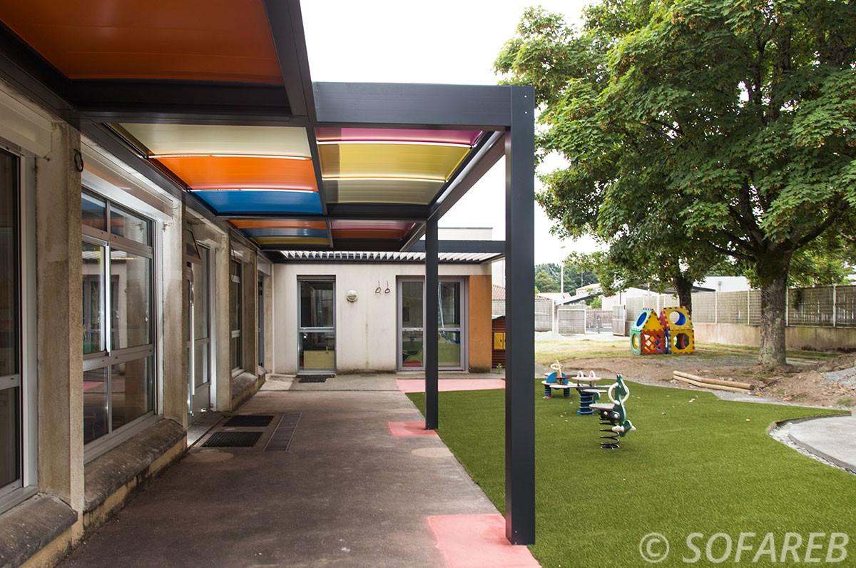pergola pour école primaire avec éléments colorées pour enfants adossée avec école primaire sur la coure pour enfant