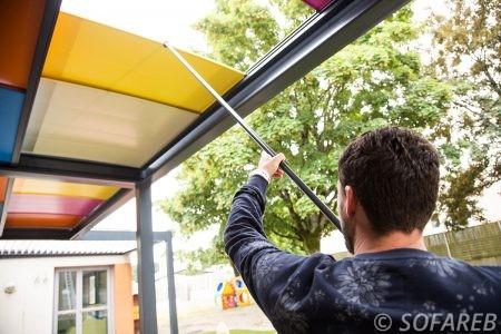 pergola colorée pour école primaire avec plaquette de couleur entretiens de la pergola par un homme