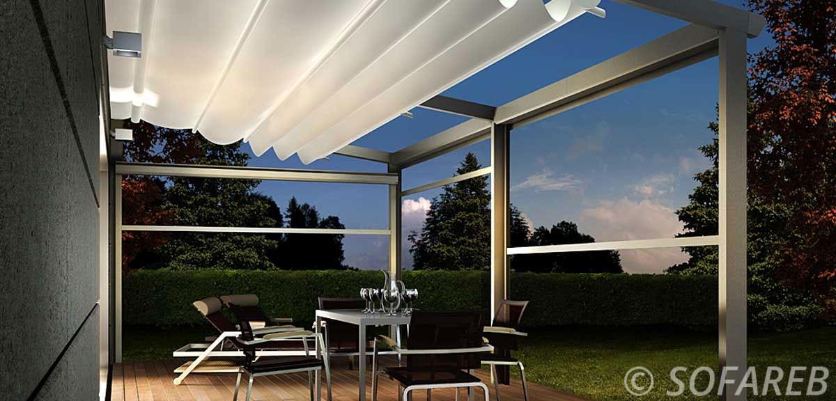 tonnelle pergola rétractable adossé a une maison moderne en extérieur sur une terrasse avec jardin, le soir soir avec lumière extérieur