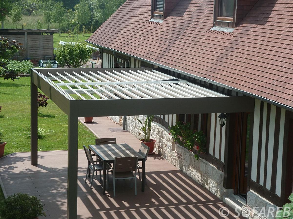 Pergola esthétique noir et blanche sur terrasse extérieur avec jardin, beaux ombrages adossées à une maison traditionnel, pergola bioclimatique