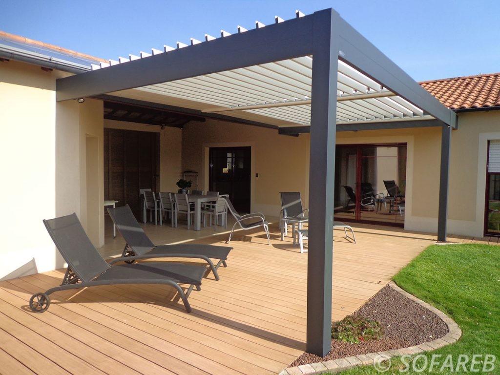 pergola bioclimatique noir racroché a une maison sur une terrasse en bois lumineuse en extérieur