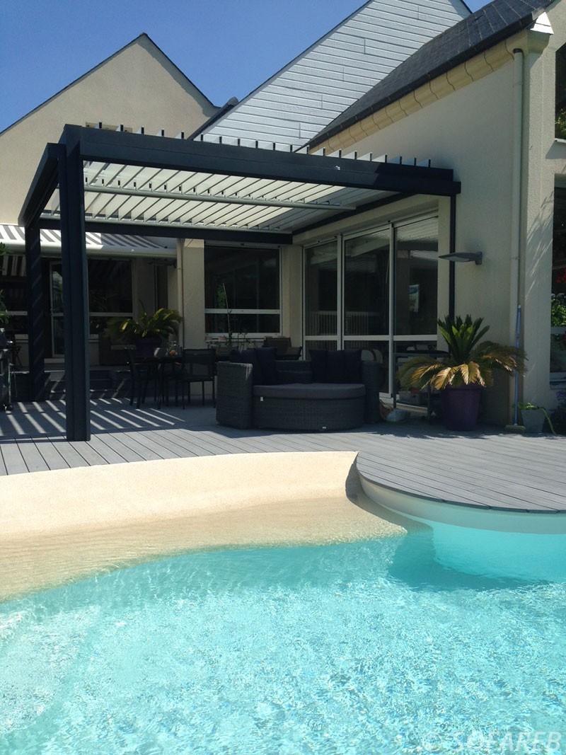 pergola bioclimatique noir adossé à une maison style bretonne sur une terrasse en bois avec piscine creusé