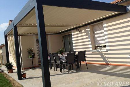 pergola blanche et noir bioclimatique adossé à un maison basique avec terrasse et jardin ombrage