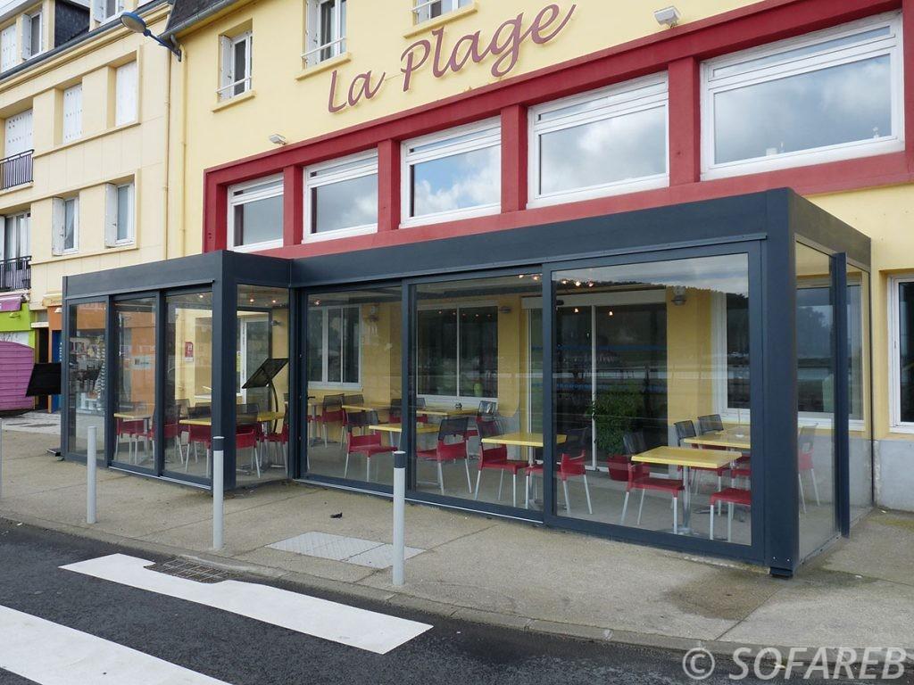 pergola vitrée noir d'un restaurant avec vu sur la rue