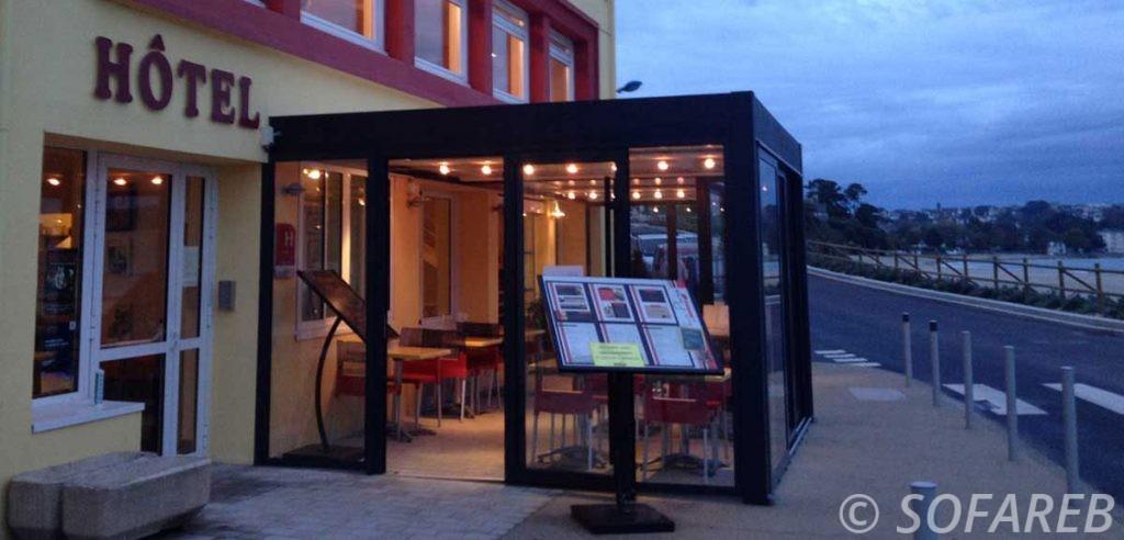 pergola bioclimatique noir et blanche beaux ombrages à coté d'une rue avec table de restauration ensoleillé