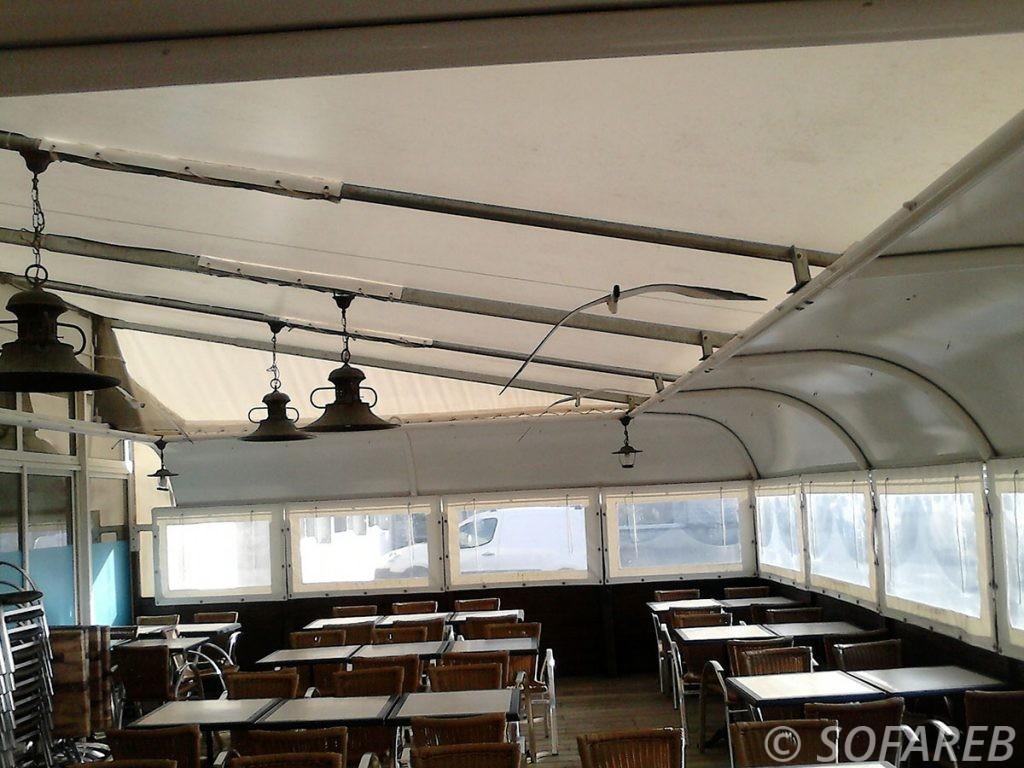 Pergola en toile blanche adossé à un restaurant, restauration avec table pour protéger de l'éxterieur