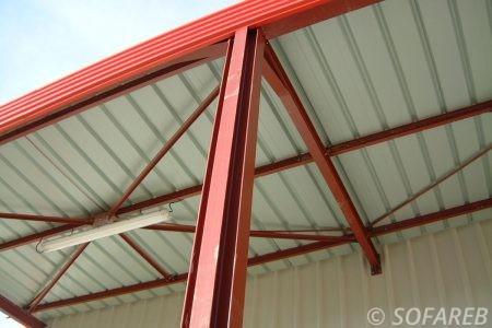 pergola professionnel en métal rouge et blanche adossé à un bâtiment en métal style an-gare