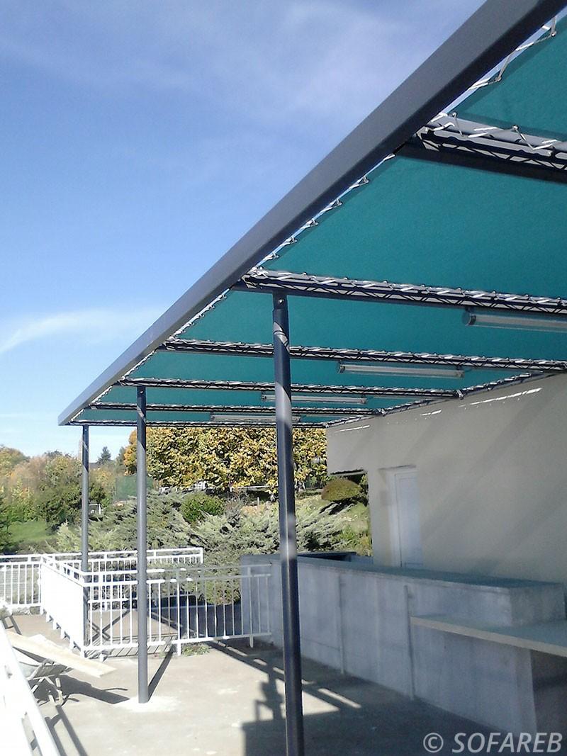pergola métallique avec toile tendue bleu adossé à un bâtiment toile opaque