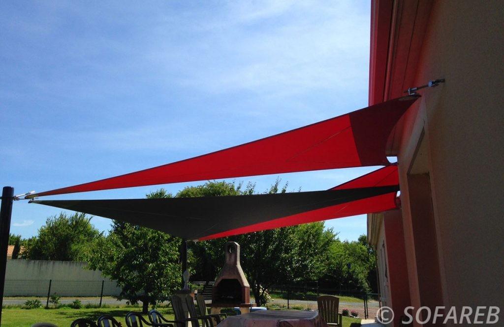 Trois belles voiles d'ombrage rouges et noires vue de prés