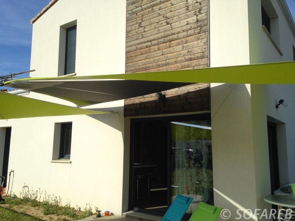 Voiles dombrage triangulaires vertes et noires accrochées à la devanture dune maison neuve