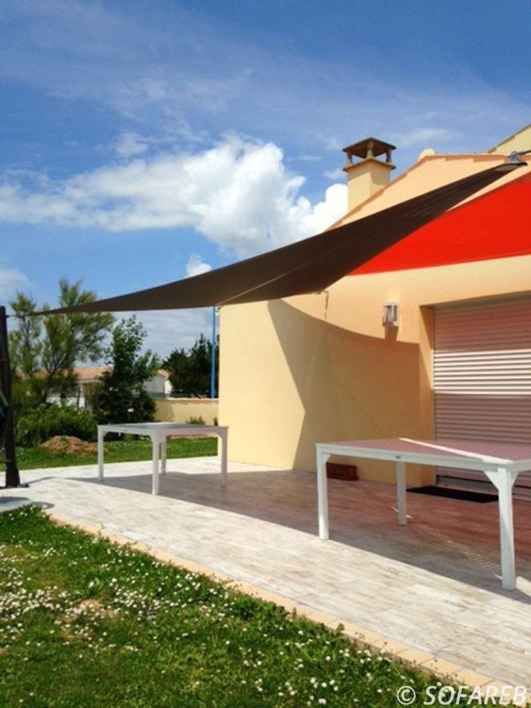 Deux voiles dombrage triangulaires qui protègent la terrasse la terrasse en bois dune maison vendeenne
