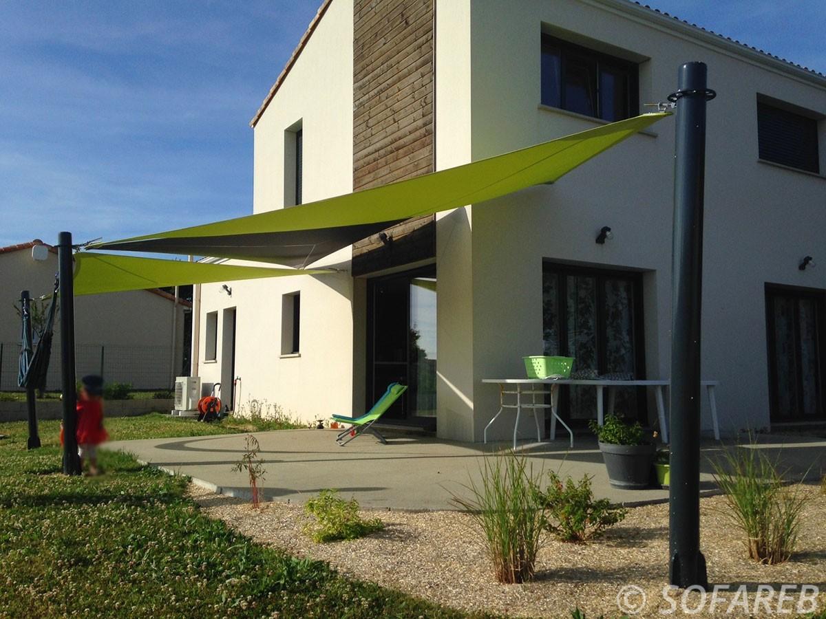 Vue de trois grandes voiles dombrage triangulaires vertes et noires composées de tissus Serge Ferrari et adossées à une maison contemporaine