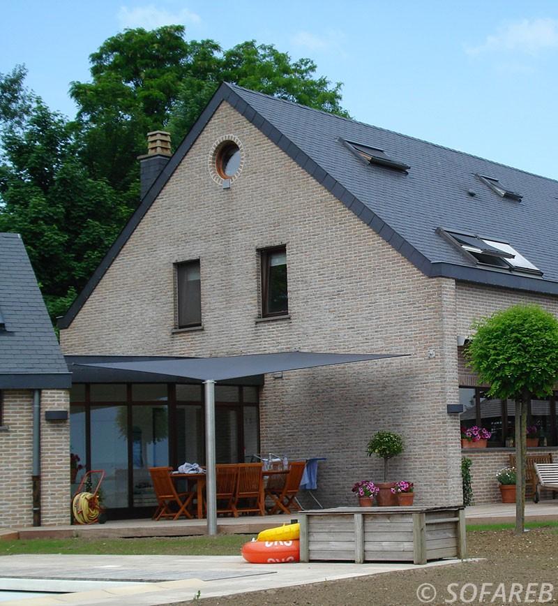 Large voile dombrage rectangulaire noire vue de loin et adossée à une grande maison en pierre
